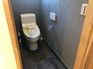 グレーの漆喰と石畳のようなタイルのトイレ