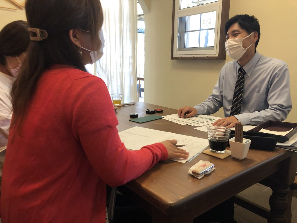 新築契約の調印式でよい笑顔をみせる内田さん