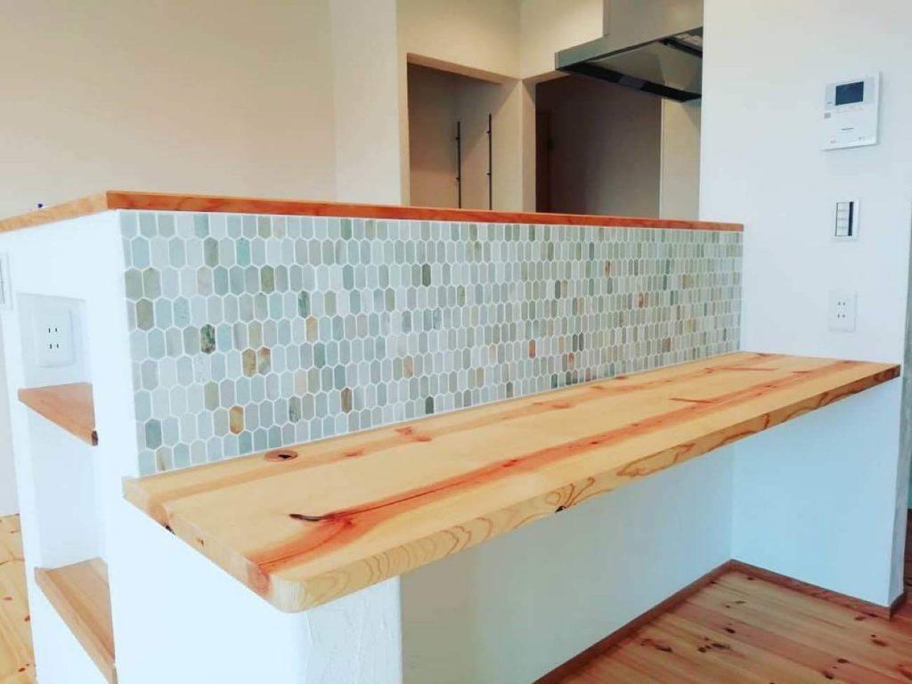 キッチン前の無垢カウンターとタイル仕上の腰壁