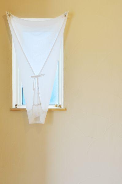 玄関に設けた明り取り窓。カーテンの付け方も可愛らしい