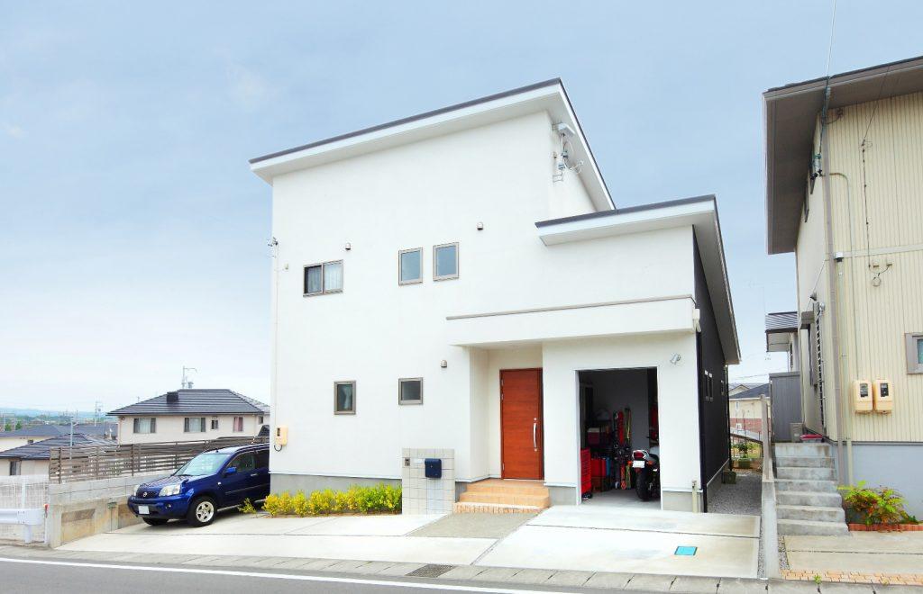 ガレージやバルコニーを付け、自然素材をふんだんに散りばめた家