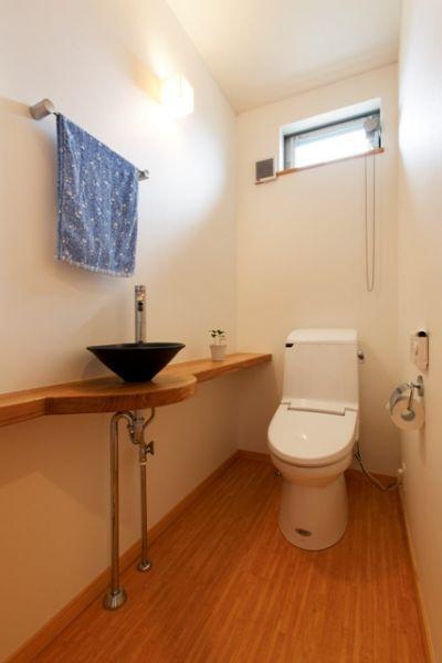 広々1.5帖のトイレ。無垢カウンターと焼き物の手洗いは、まるでオシャレな居酒屋にいるかのよう。
