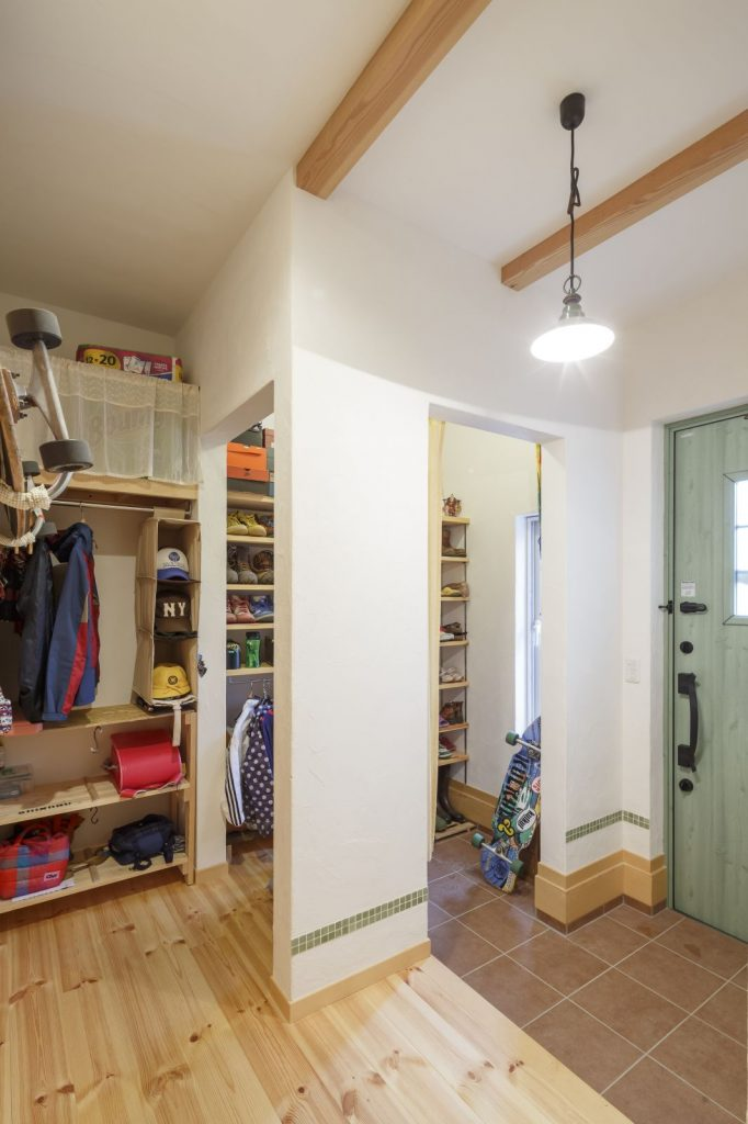 緑の木製ドアがアクセントの玄関は収納スペースたっぷり