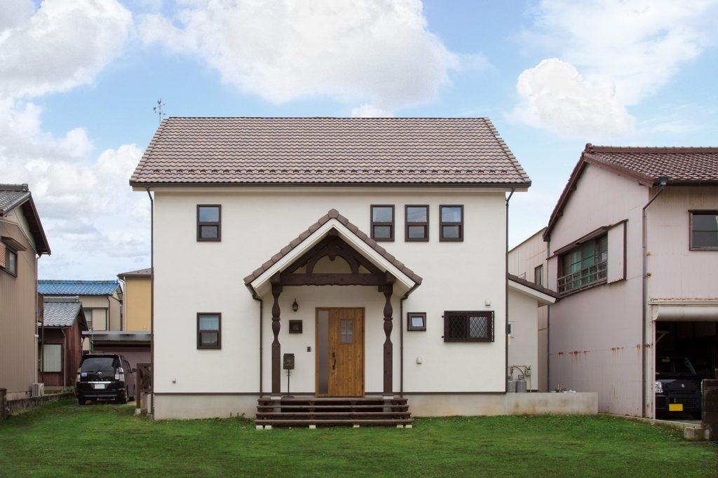 切妻屋根と玄関ポーチの組み合わせが、英 国の田舎町に佇んでいるかのような外観