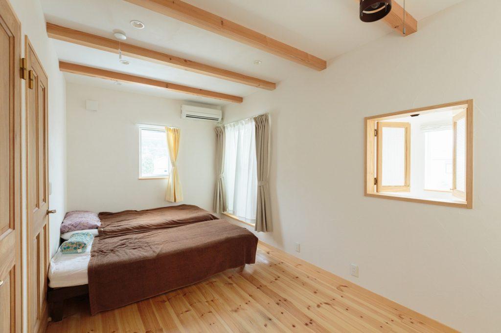 リビングの吹抜けと可愛らしい窓でつながる寝室