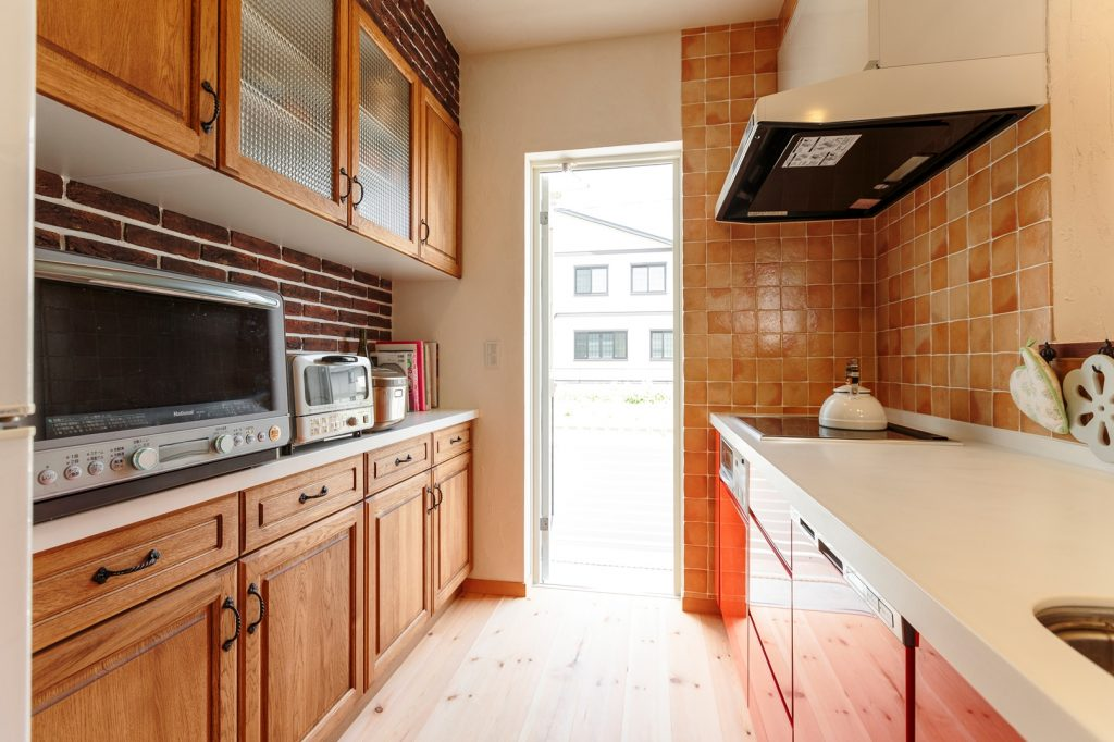 カップボードはレンガと合わせ木目に。キッチンはお手入れがしやすいような扉をセレクト