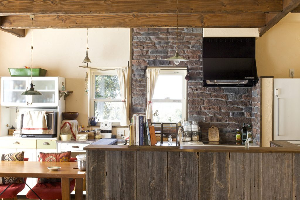 アンティークの食器棚とよく似合う、古材とレンガを組み合わせた手作り感あるオープンキッチン。