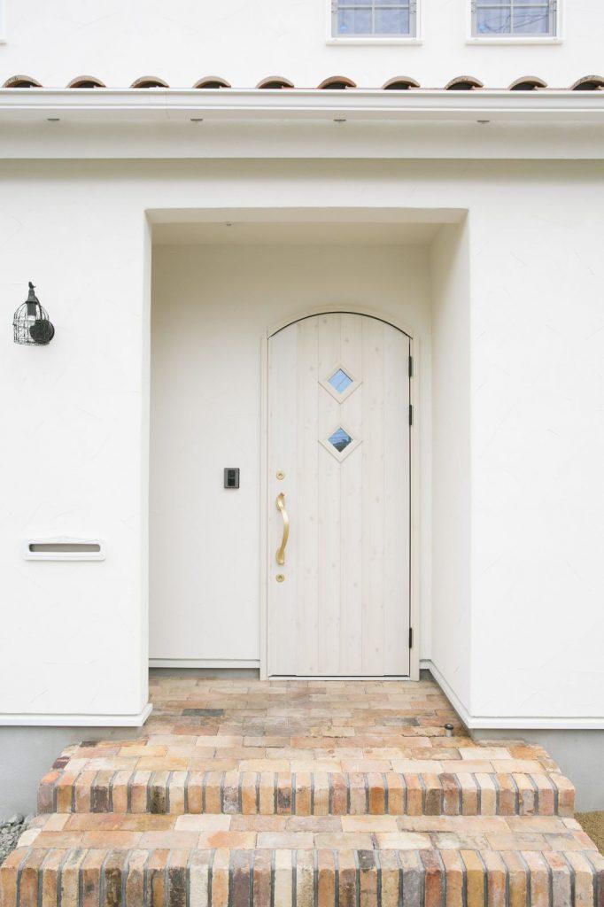 天面が弧を描く白い木製ドアが可愛らしくロマンチックな雰囲気
