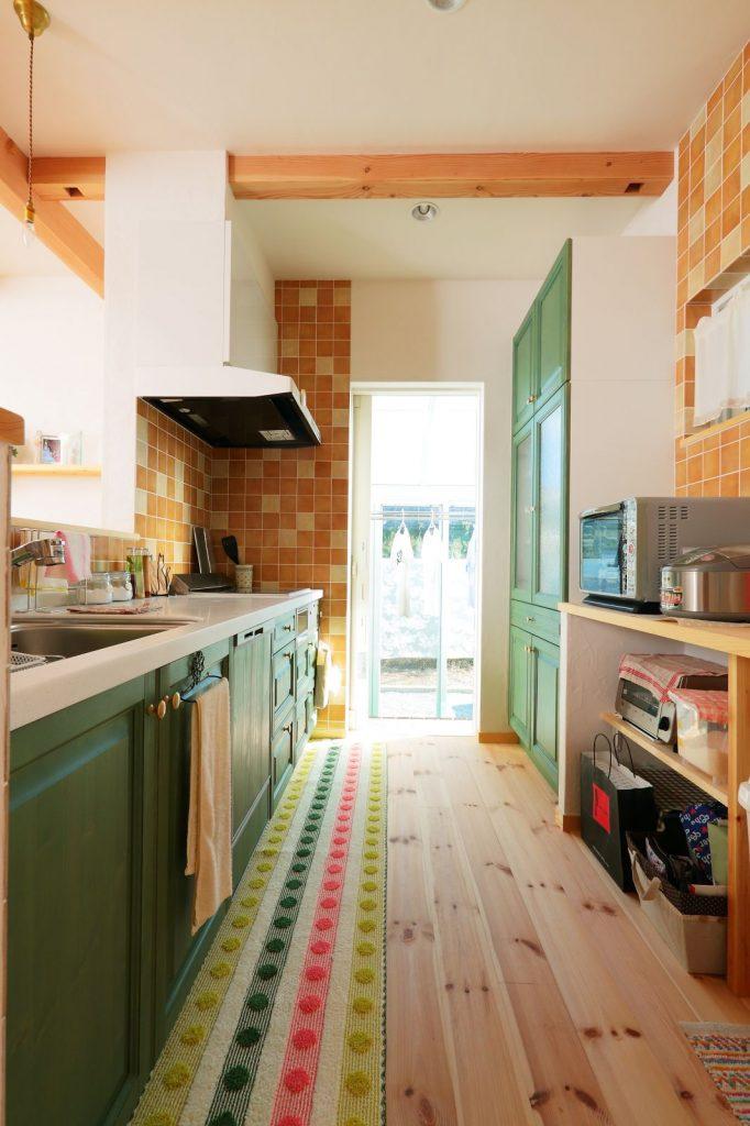ショールームを参考にしたキッチン。木と白い塗り壁に深いグリーンがよく似合う