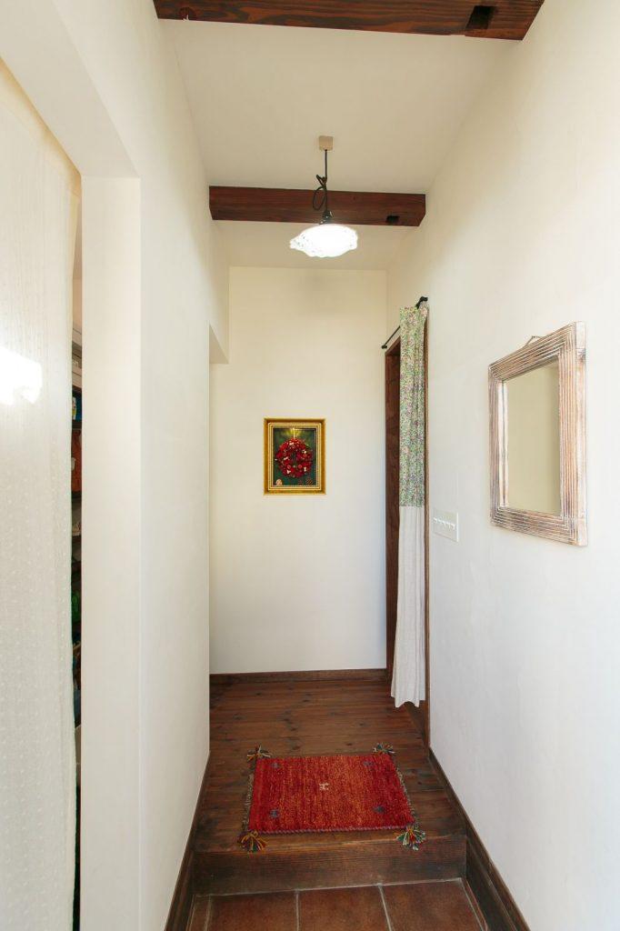 白い塗り壁に梁や床の木のレトロ感が映える玄関