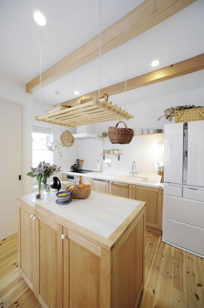 奥様こだわりのアイランドキッチン。作業台上の吊棚はご主人の手作りだとか