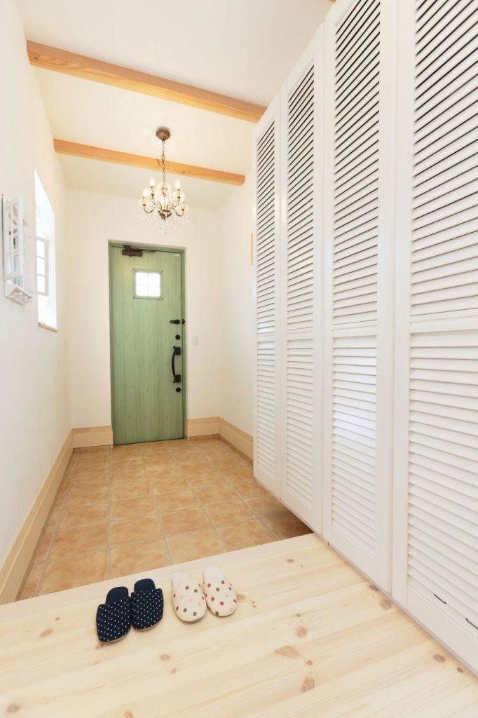 白色の中にモスグリーンのドアがアクセントになった玄関