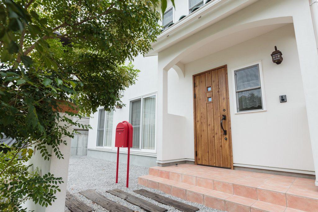 白い塗り壁と緑色の屋根に、茶色い木目のドアがアクセントになった外観