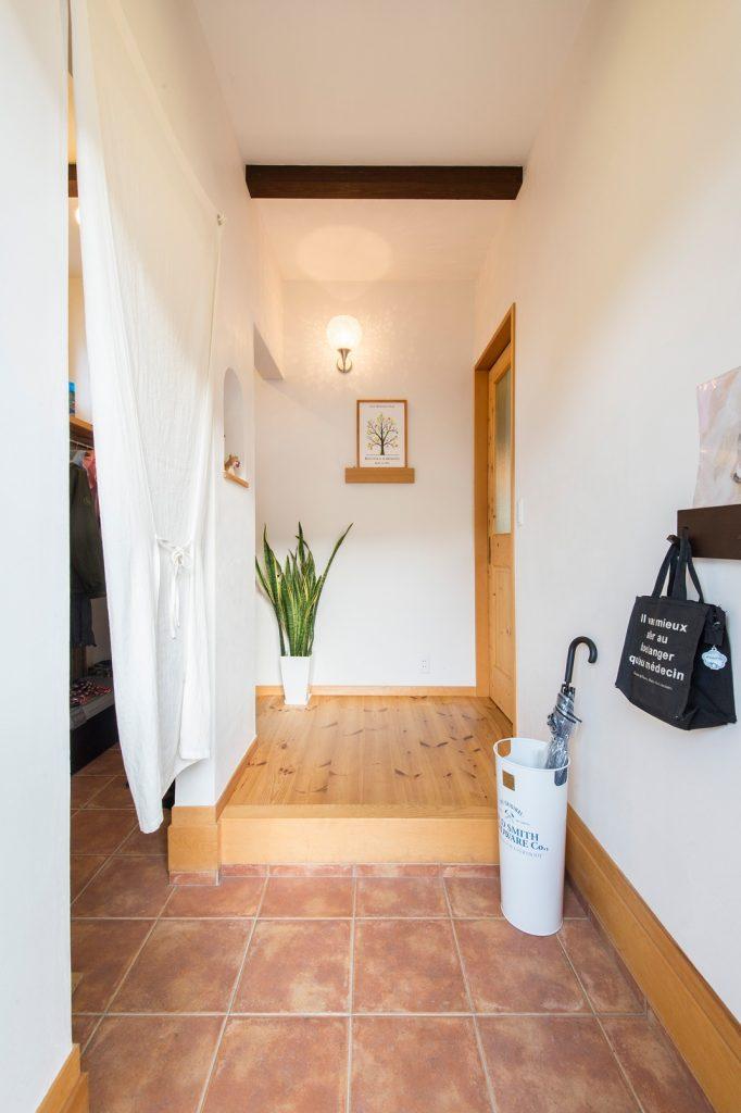 素敵な絵がお出迎えしてくれる玄関。壁に映る照明の光で、より華やかな印象に
