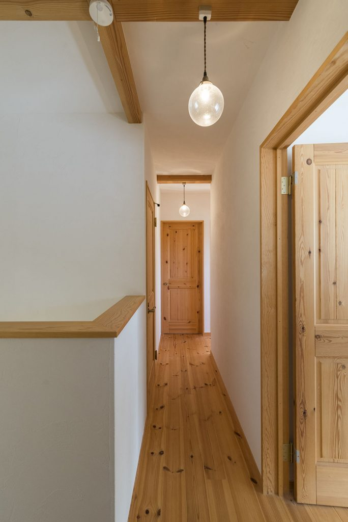 自然素材のナチュラルな空間の中に丸い照明がアクセントになった2階のホール