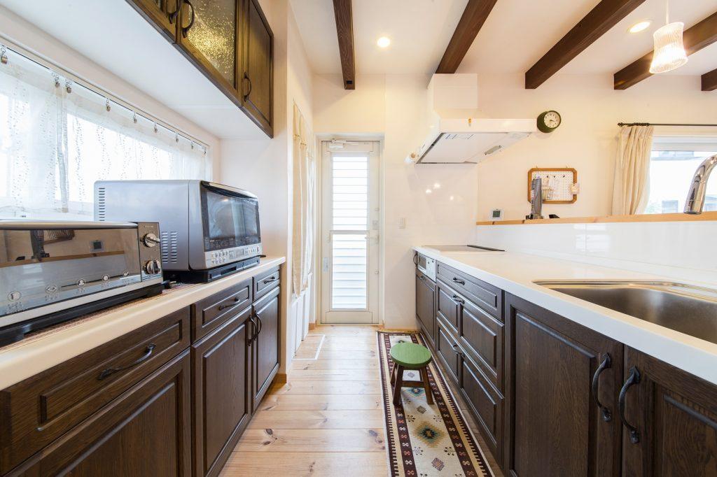 キッチン扉と、天井の梁のカラーを合わせて一体感のある空間に