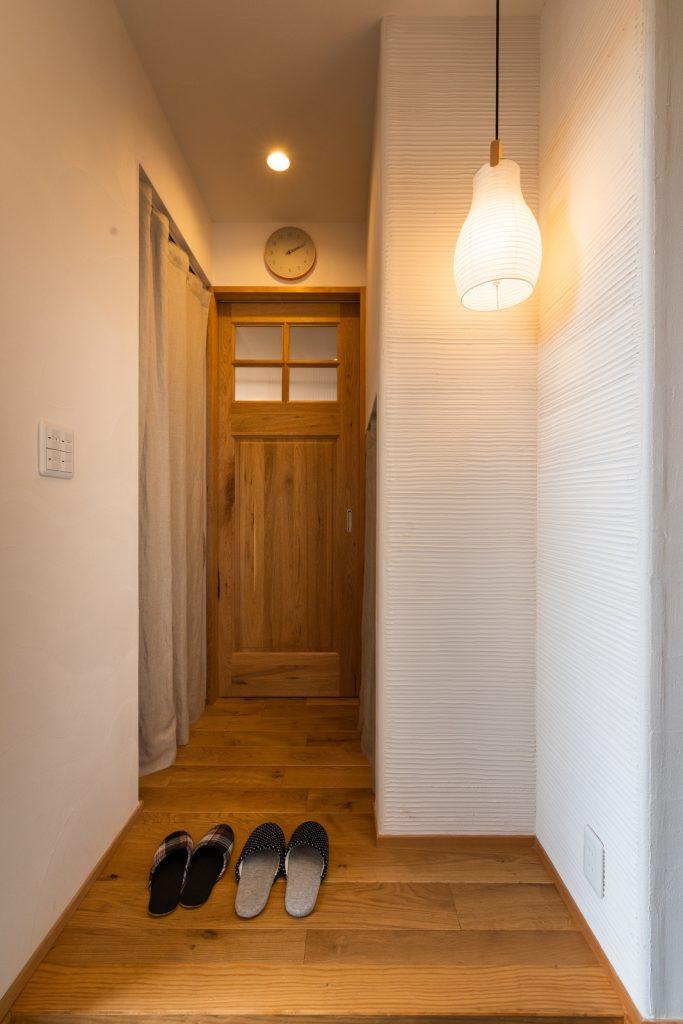 漆喰壁に照明が映える玄関