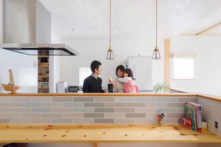 かわいい照明とやさしい色のタイルが素敵なキッチンと相性の良い漆喰壁
