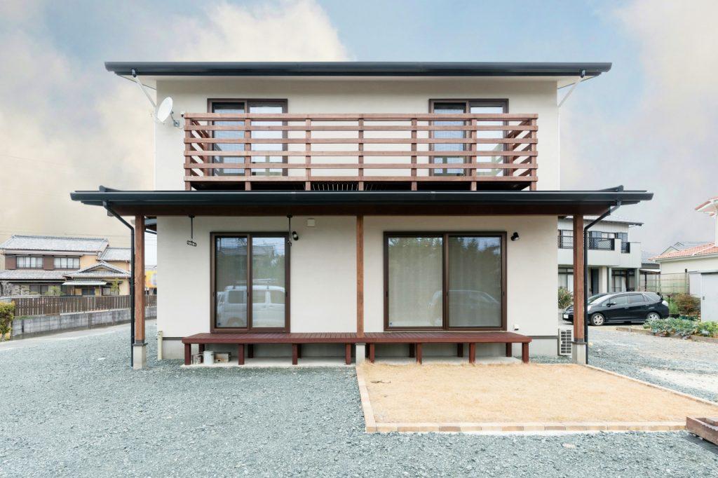 木製ベランダと塗り壁の自然素材住宅