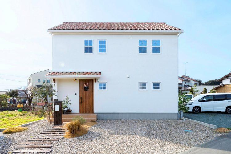 オレンジ色の屋根と白色の塗り壁に木製の玄関がかわいい総二階プロヴァンスのマイホーム
