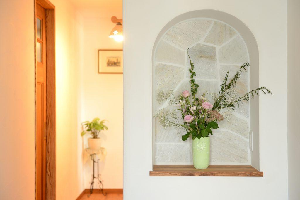 玄関では、石張りのニッチがお客様をお出迎え。日替わりで、ご主人様のコレクションや奥様セレクトのお花が飾られる