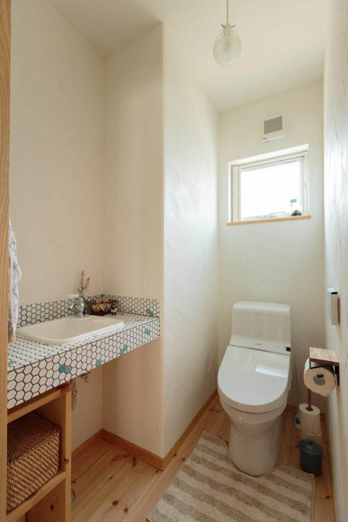 トイレの手洗いカウンターは、白と水色の六角形のモザイクタイルで遊び心をプラス