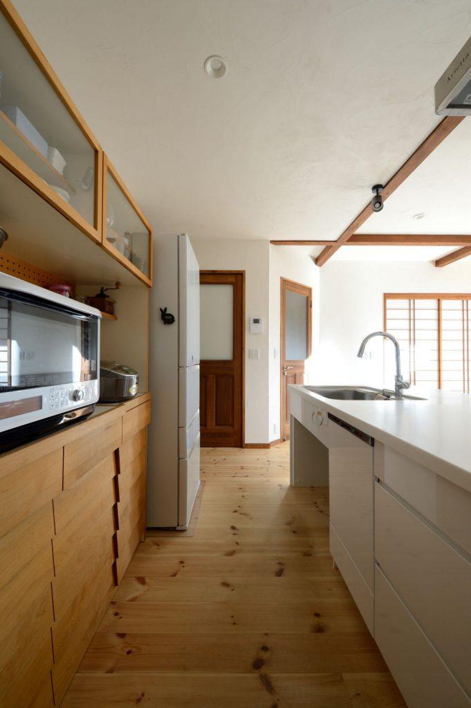 """LDKの様子がよく見えるオープンキッチン。""""お持込み""""のカップボードも室内の雰囲気と調和している"""
