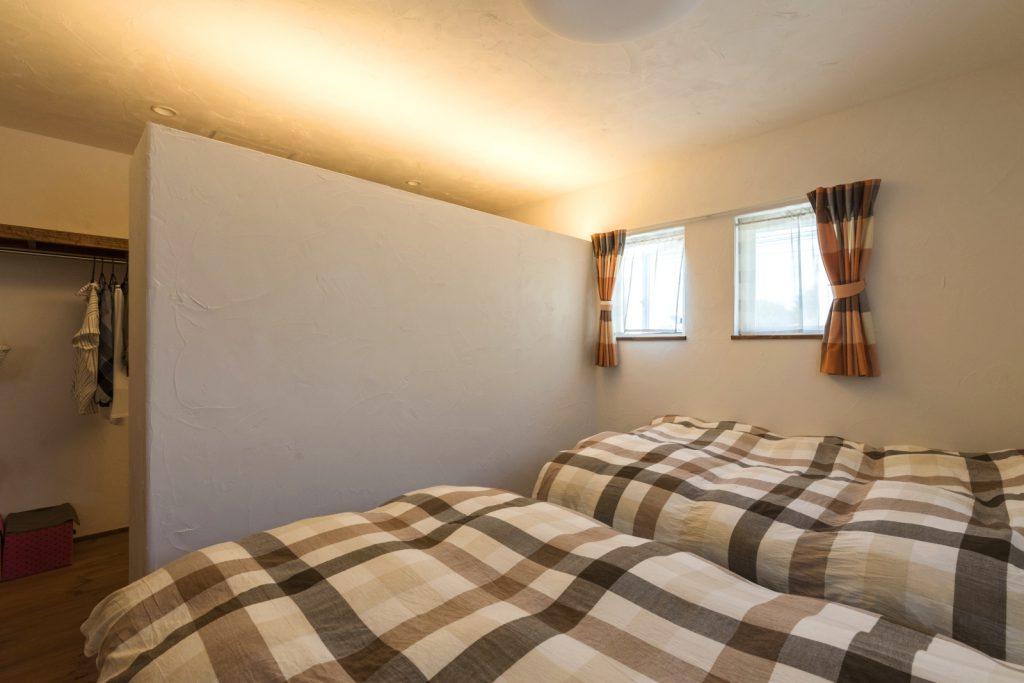 漆喰が美しくライトアップされた落ち着きのある寝室