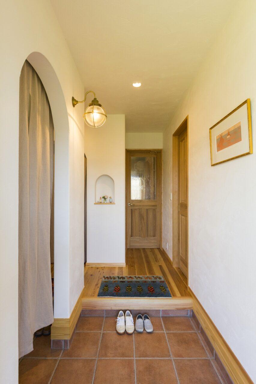 丸い照明がアクセントのシンプルな玄関