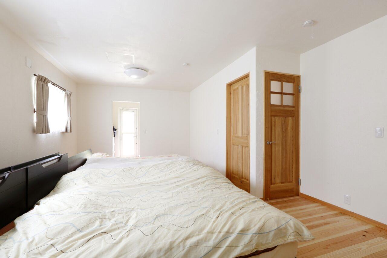 白い漆喰で清々しい雰囲気の寝室。お子様の成長に合わせて部屋を分割できるようドアを2か所に取り付けた