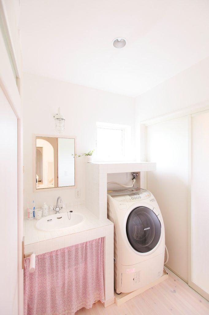 洗面カウンターと洗濯機の上の棚を一体にして、統一感を演出。