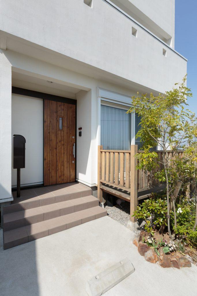 南向きの明るい玄関とウッドデッキ。 ウッドデッキには手すりを付けて、安全性・デザイン性もUP