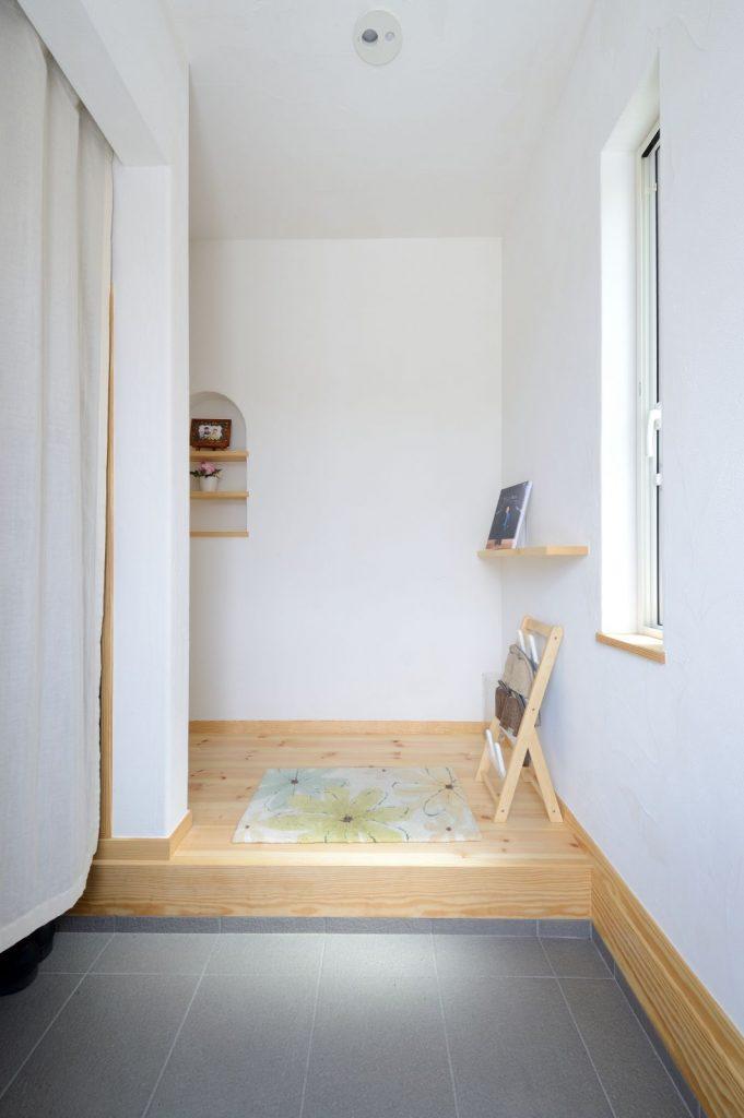 漆喰の塗り壁が気持ちいい玄関。左手はシューズクローク