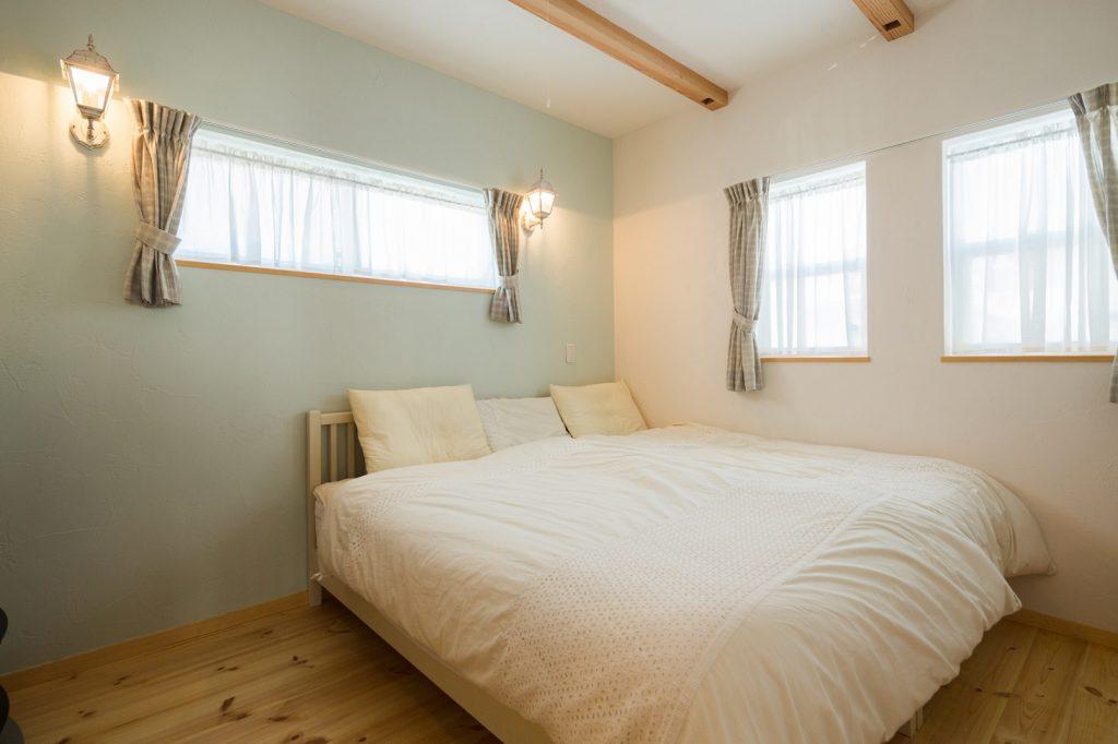 ぐっすり眠れる寝室。一面だけ色をかえた青い塗り壁と照明が奥様のこだわり