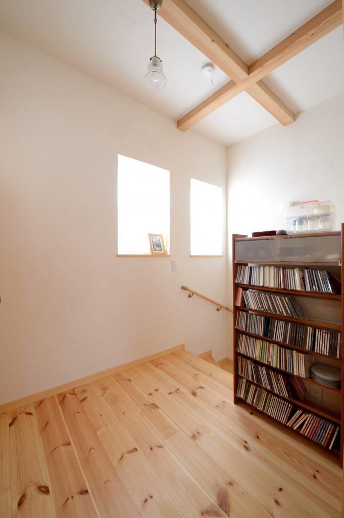 階段ホールには本棚を置き、家族の共用スペースに