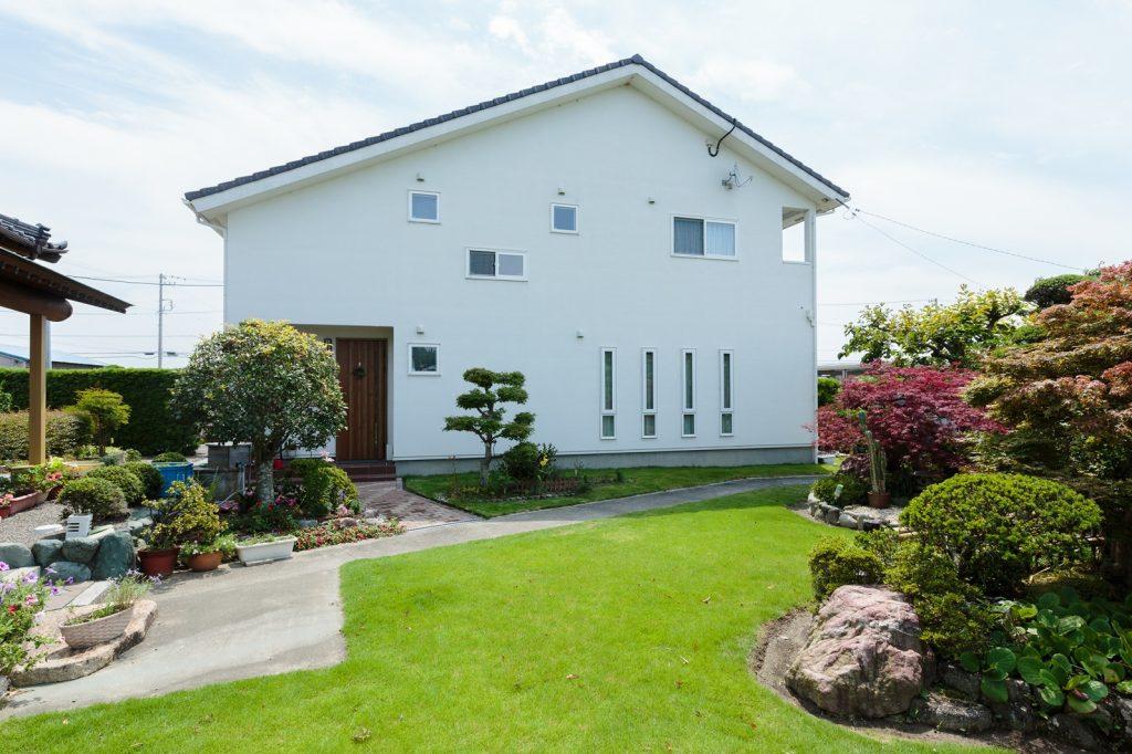 お庭の緑が映える、真っ白い塗り壁のシンプルな外観