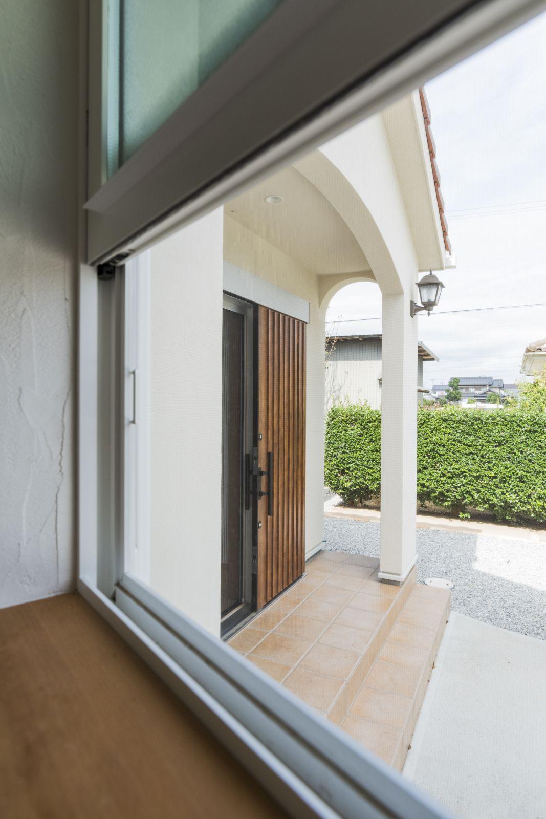 シンプルなドアとアーチの垂れ壁がマッチした玄関