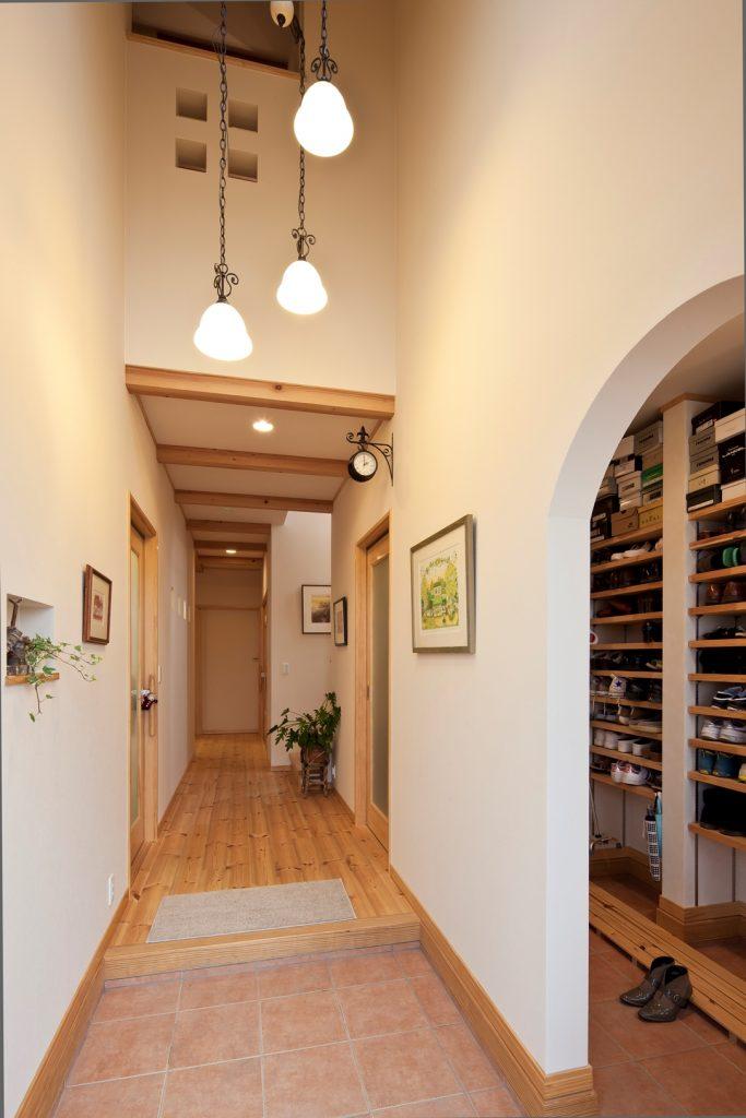 玄関の上部は勾配天井・吹き抜けで開放的に。シューズクロークも設け、すっきりとした印象に