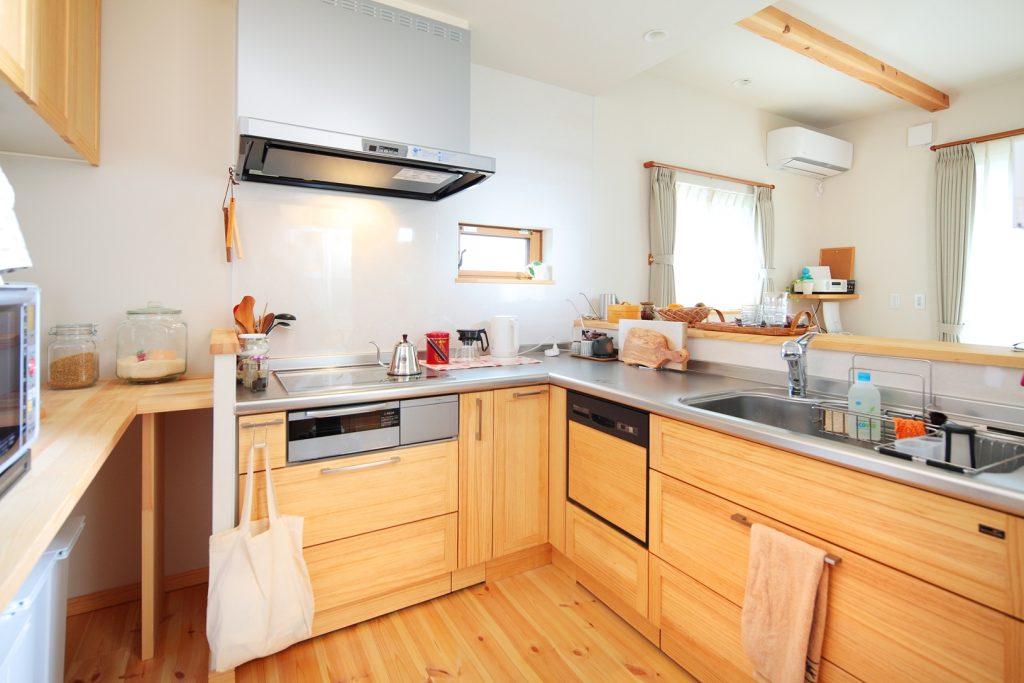 統一感のある木製扉でまとめられたL字型キッチンは奥様のお気に入りの場所。