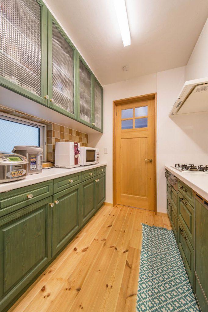 開放的な間取りと心落着くグリーンのキッチンのある住まい