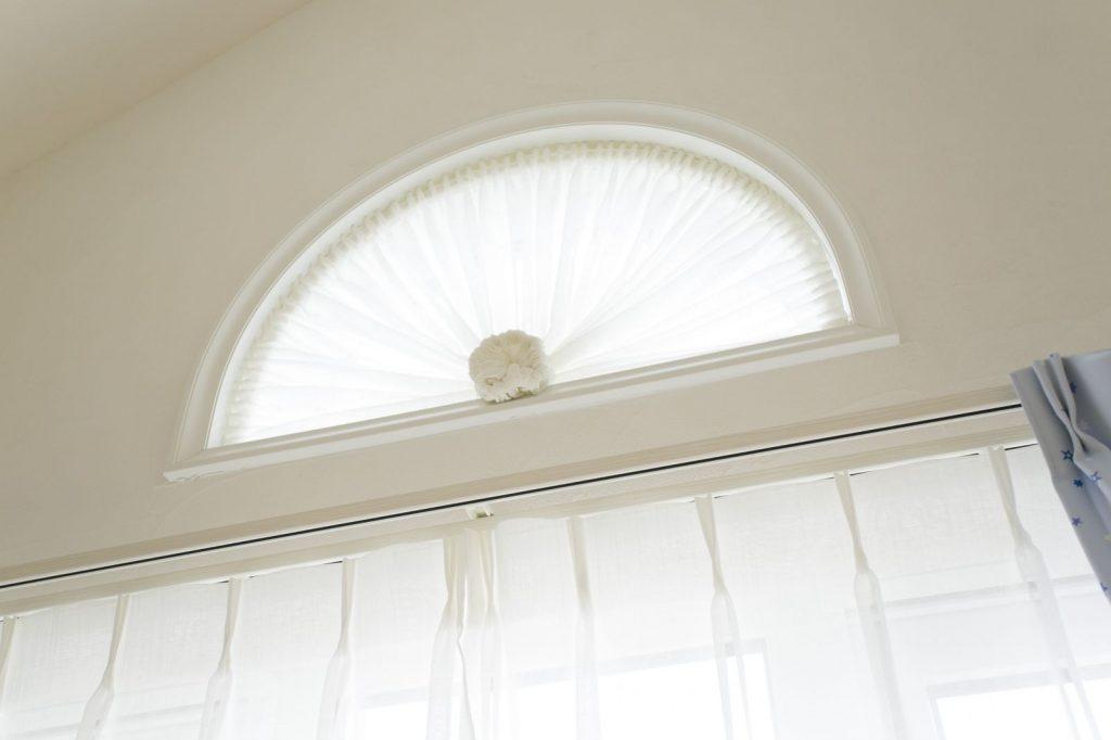 輸入住宅をイメージした洋風の白いサッシと半円形の窓は、外観のおしゃれなアクセントになっている。