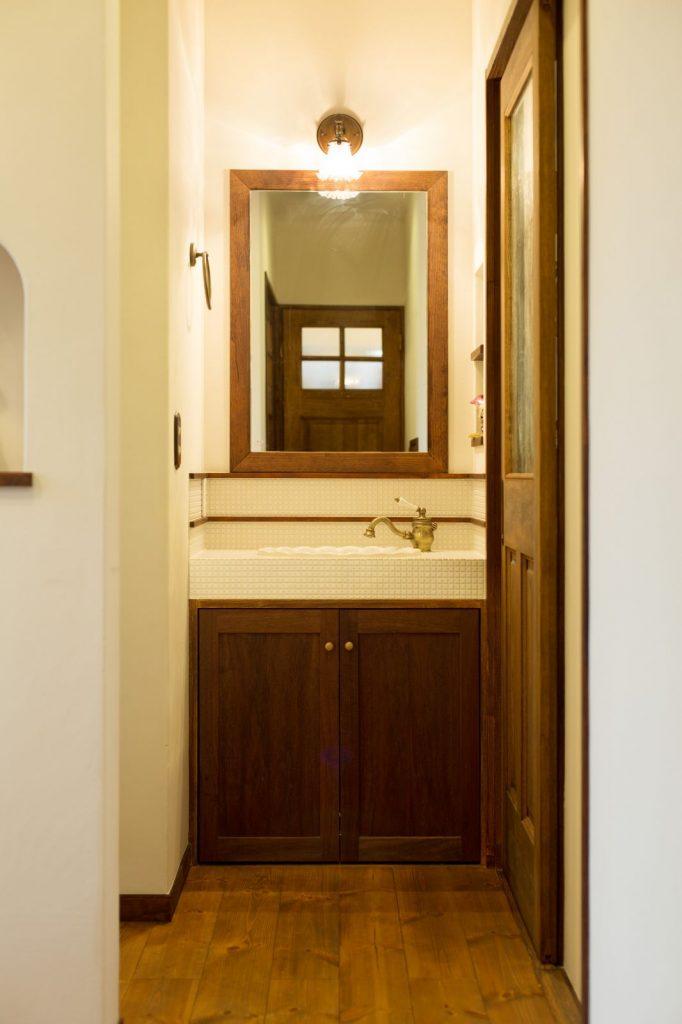 白いモザイクタイルでシンプルに仕上げた洗面スペース。アクセサリーはアンティーク調に統一