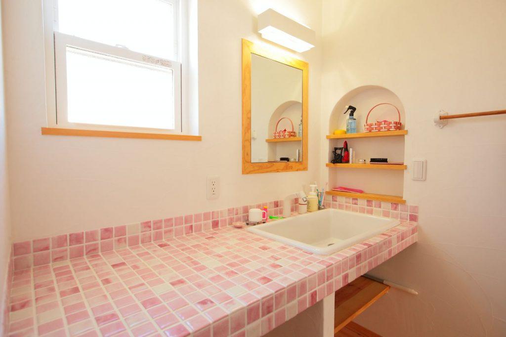 ピンクのモザイクタイルやR型の埋め込み棚がキュート!