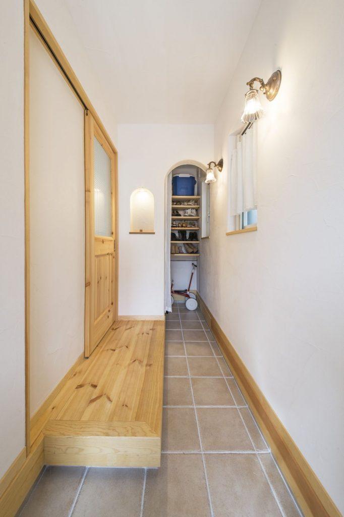 細長い玄関は土間のようなつくり。奥にはシューズクロークを設けてたっぷりと収納できる。