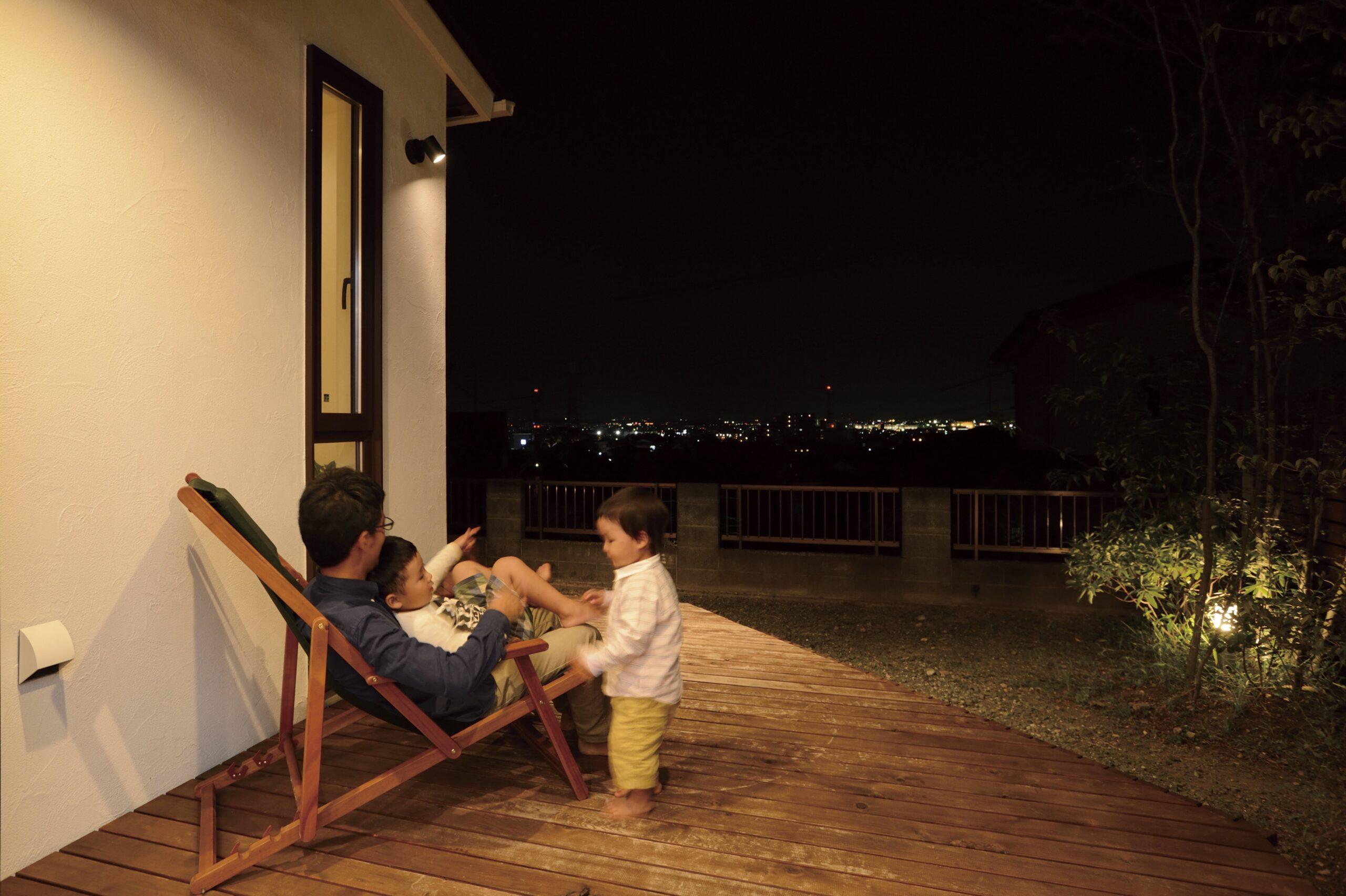 夜のウッドデッキで景色を楽しむ