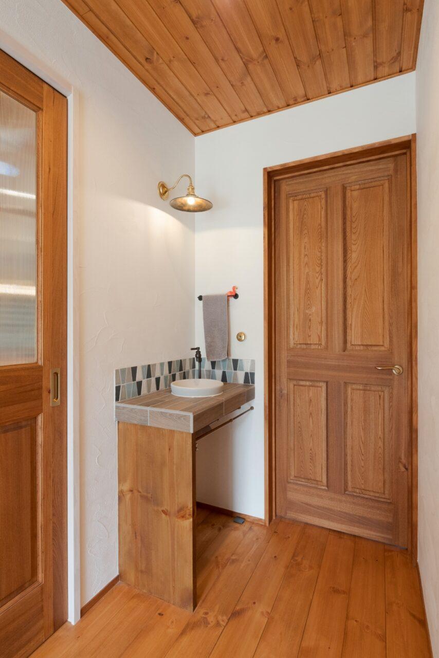 可愛いブルーのタイルが並ぶ玄関前の洗面