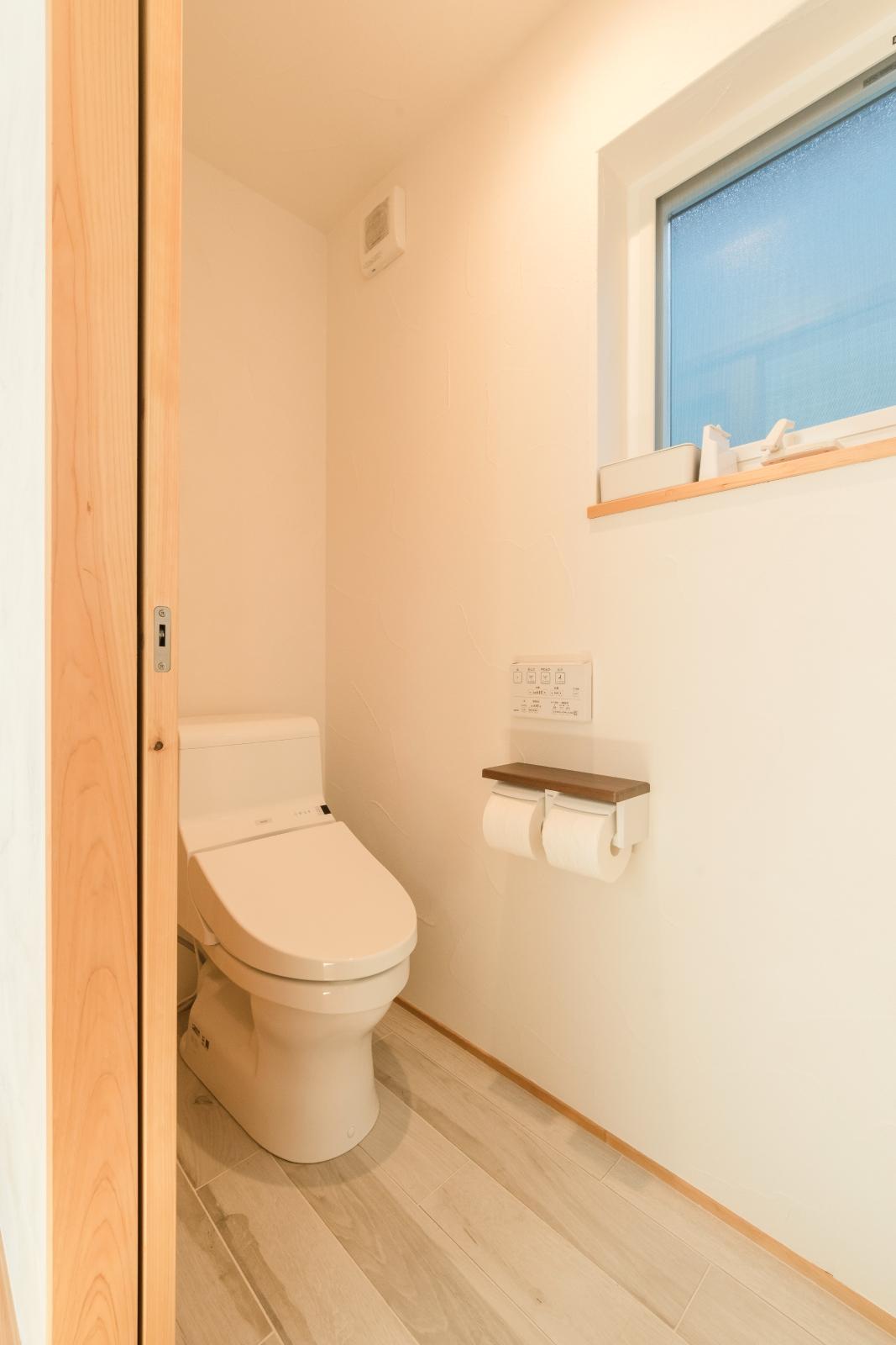 やさしい色の床タイルでお手入れしやすいトイレ