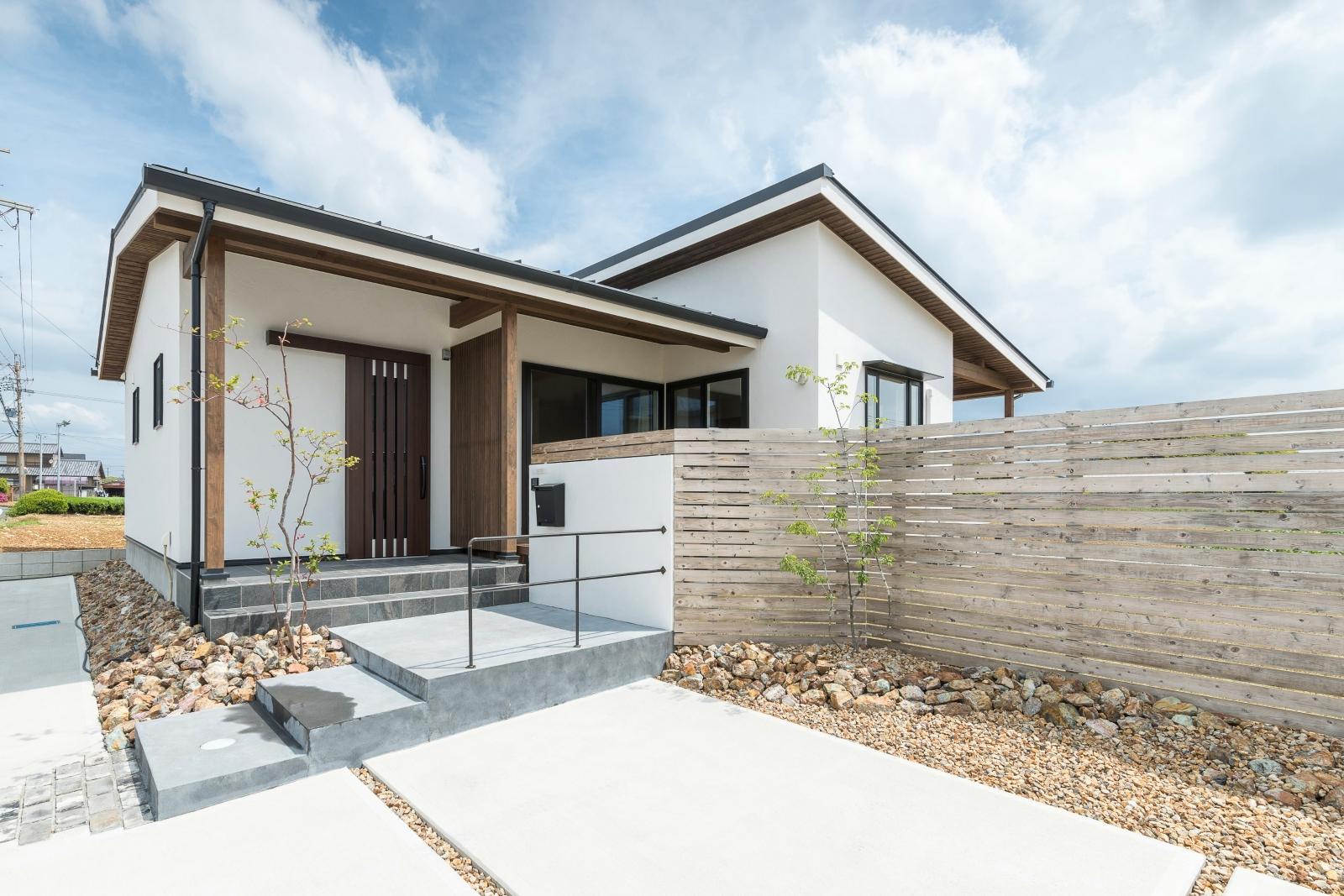 玄関横の木格子と木塀がバランスよく配置され、プライバシーを守りつつ開放的な空間を演出する美しいフォルムの平屋