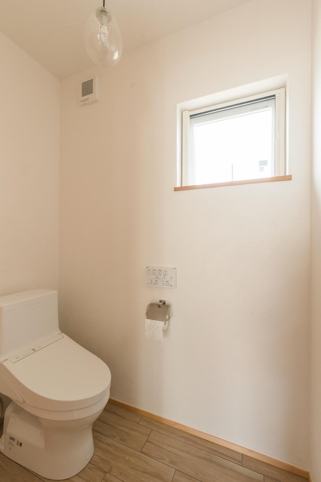 遊び心のある照明と床タイルのトイレ