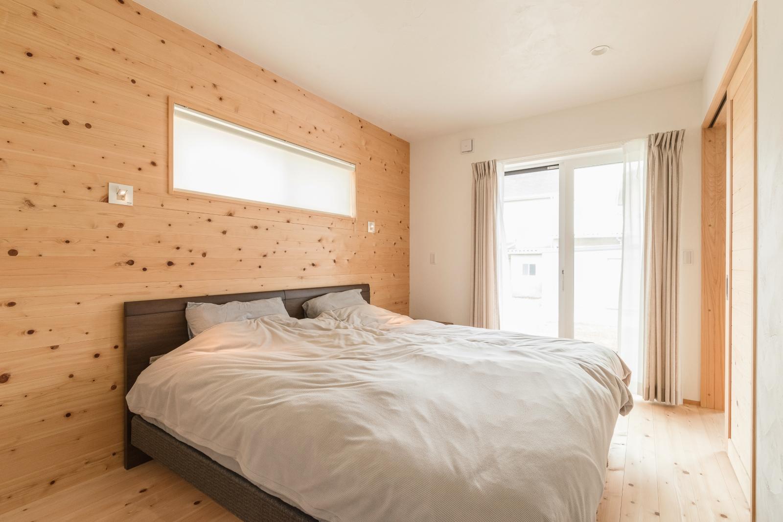 枕元に折りたたみ式照明のある板張り壁の寝室